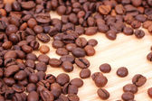Coffee beans on wooden board — Stock Photo