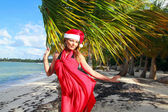 Santa woman on tropical beach — Stock Photo