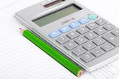 Calculator and pencil on notebook — Stock Photo