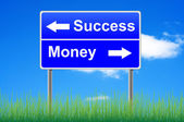 Success money roadsign on sky background, grass underneath. — Stockfoto
