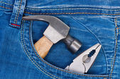 Hammer and pliers in pocket jeans. — Stock Photo
