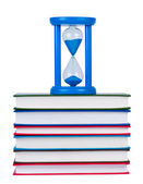 Hourglass on pile of books isolated on white background. — Stock Photo