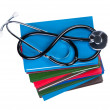 Medical stethoscope on pile books isolated. — Stock Photo