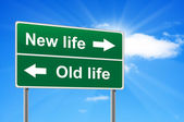 New life old life road sign on background clouds and sunburst. — Stock Photo