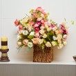 Composition with artificial flowers bouquet in wattled vase — Stock Photo