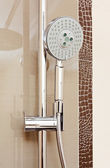 Metal shower tap in modern bathroom with brown ceramics tile — Stock Photo