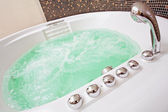Jacuzzi with swirling water and brown mosaic in bathroom — Stock Photo