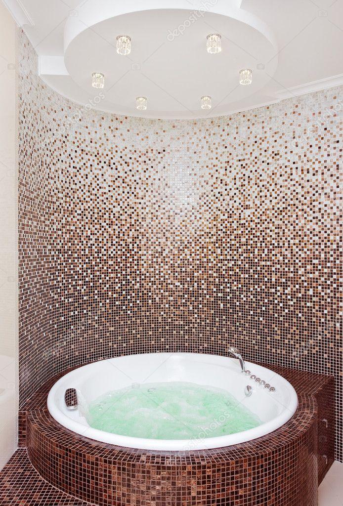 Jacuzzi rotonda bianca nel moderno bagno con mosaico marrone e ...