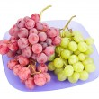 Red and white grapes bunches on blue plate isolated on white - Stock Photo
