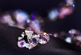 Diamond (small purple jewel) stones heap over black silk cloth b — Stock Photo