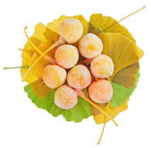Ginkgo Biloba fruits heap over leaves isolated on white — Stock Photo