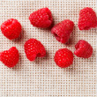 Many red ripe raspberry fruit, on gray linen table cloth with co — Stock Photo