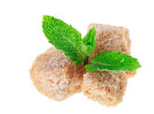 Three brown lump cane sugar cubes with peppermint leaves, isolat — Stock Photo