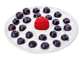 Red raspberry and blue bilberry in small round plate with sour c — Stock Photo
