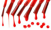 Set of red nail polish brushes and drops isolated on white — Stock Photo