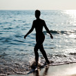Woman silhouette on sea beach — Stock Photo