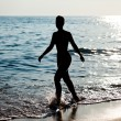 Woman silhouette on sea beach — Stock Photo #7254155