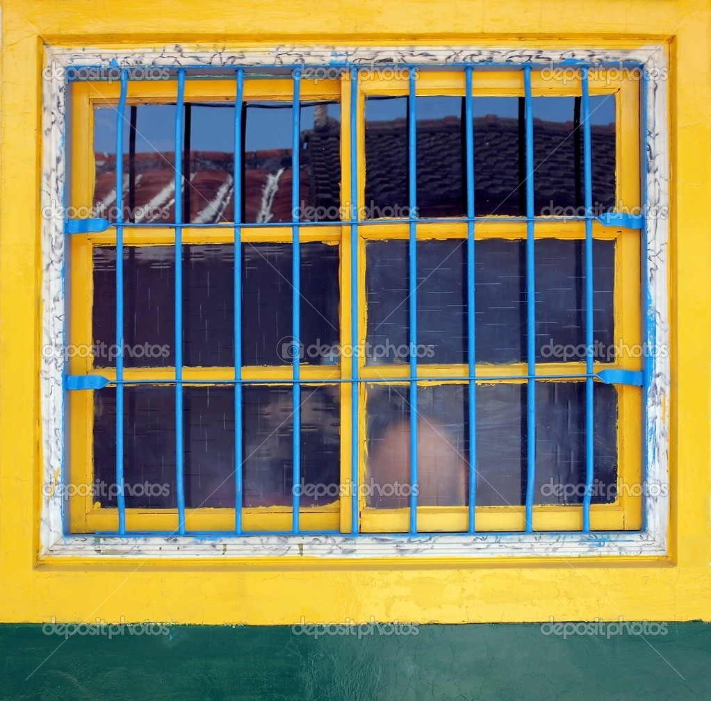 An old window with yellow frames and blue iron bars — Stock Photo #7833505