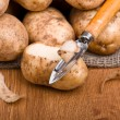 Fresh potatoes is peeled with a kitchen knife — Stock Photo #7178498
