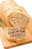 Slice of homemade bread with pate and herbs on a wooden cutting — Stock Photo