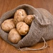 Harvest potatoes in burlap sack, sideways — Stock Photo