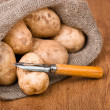 Potatoes with knife to clean the vegetables on the natural backg — Stock Photo #7947434