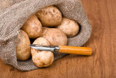 Potatoes with knife to clean the vegetables on the natural backg — Stock Photo