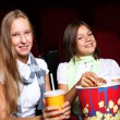 Two young girls watching in cinema — Stock Photo #6841713