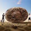 Businessman rolling a giant stone — Stock Photo #6842310