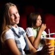 Two young girls watching in cinema — Stock Photo #6842750