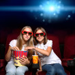 Two young girls in cinema — Stockfoto