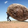 Stock Photo: Businessman rolling a giant stone