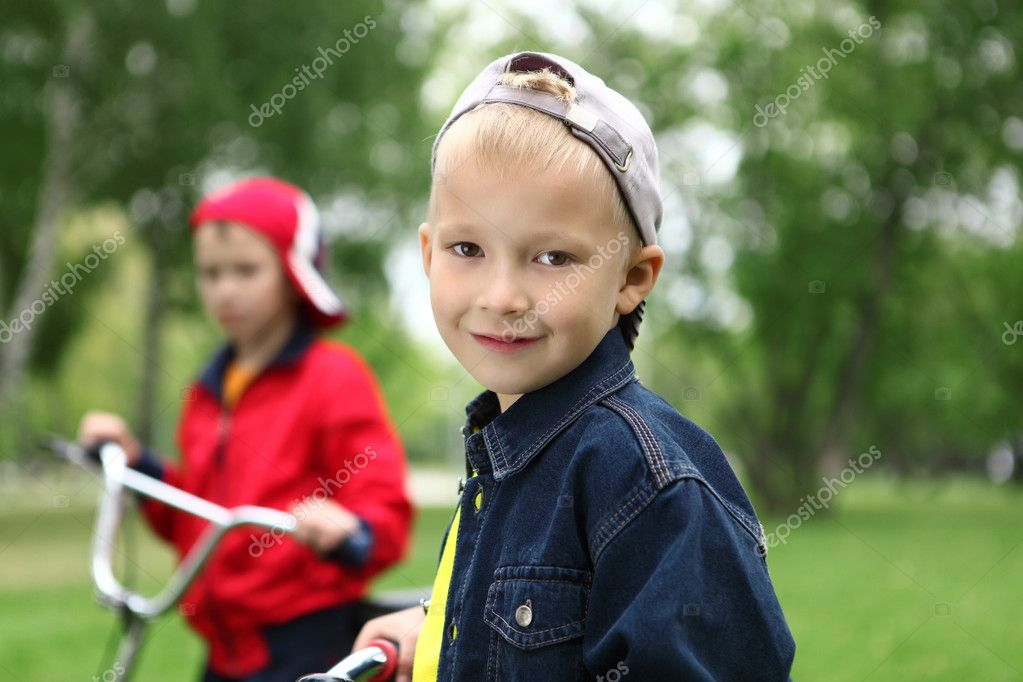 Happy smiling boy on a bicycle in the green park  Stock Photo #6842495
