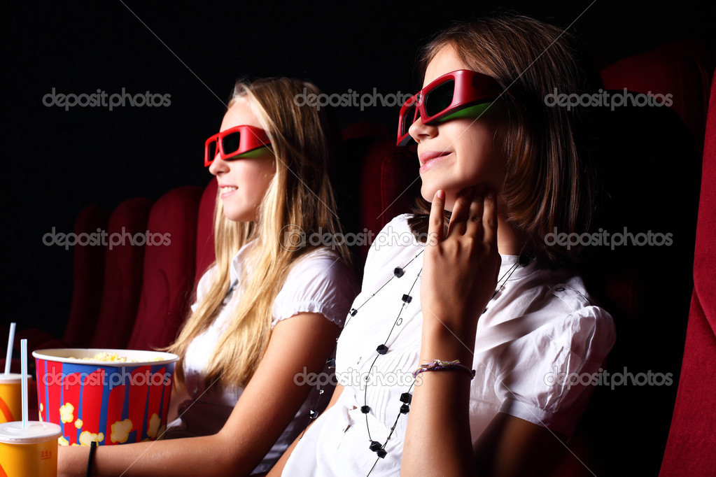 Two young girls watching movie in cinema — Stock Photo #6842565