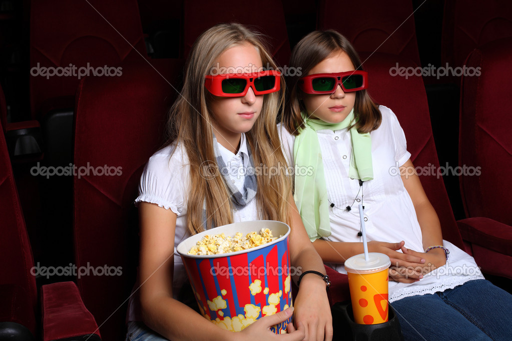 Two young girls watching movie in cinema — Foto Stock #6843180