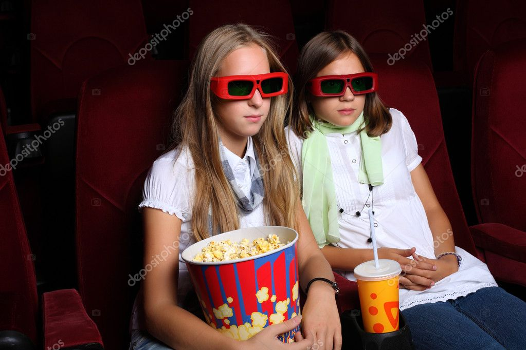 Two young girls watching movie in cinema — Stok fotoğraf #6843180