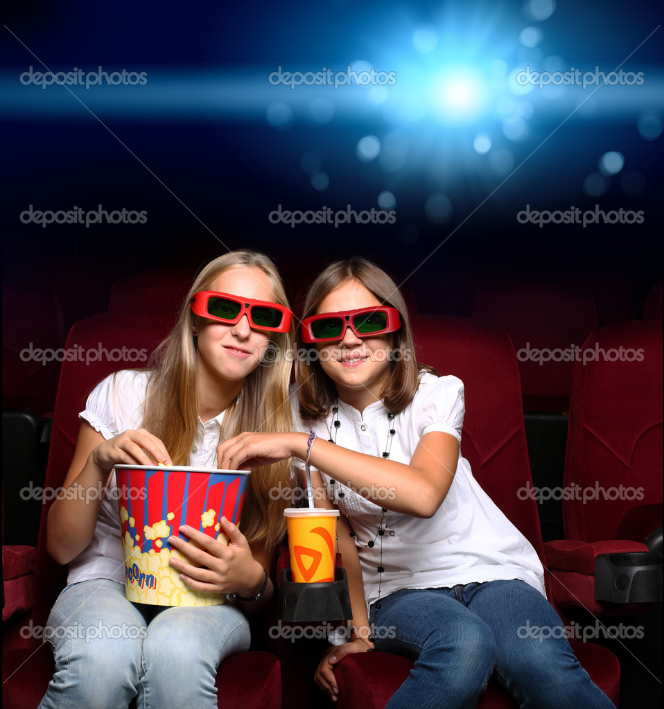 Two young girls watching movie in cinema  Stock Photo #6843554