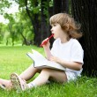 Portrait of little girl reading a book in the park — Foto de Stock