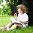 Portrait of little girl reading a book in the park — ストック写真