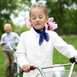 Girl on a bicycle in the green park - Stock Photo