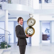 Royalty-Free Stock Photo: Businessman in office holding clock pyramid