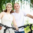 Young couple on the bikes in the park - Stock Photo