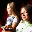 Two young girls watching in cinema — Stock Photo #6855165
