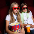 Two young girls watching in cinema - Stock Photo