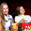 Two young girls watching in cinema — Stock Photo #6855390