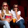 Two young girls watching in cinema — Stock Photo #6855423