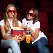 Two young girls watching in cinema — Stock Photo