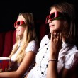 Two young girls watching in cinema — Stock Photo #6855432