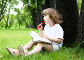 Portrait of little girl reading a book in the park — Стоковое фото