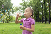 Little girl in the park blowing bubbles — Stok fotoğraf